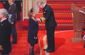 Receiving her MBE from Prince Charles